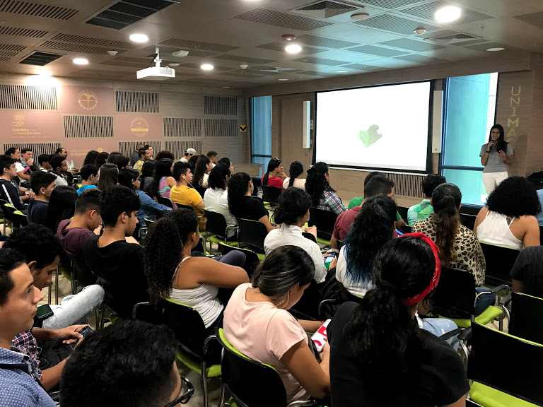A group of at least 40 students are sitting in a lecture room listening to a presentation. A large screen in the room projects the slides for the presentation. © M. Smith.