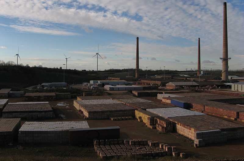 A view of a typical brick industry. Chimneys and piles of bricks are in the foreground. In the background there are wind turbines. Photo by Anna Robinson.